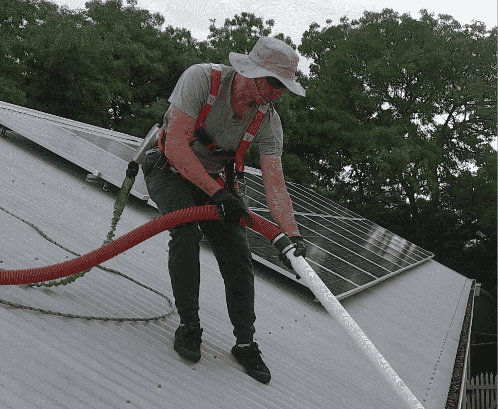 Man standing on roof cleaning gutters with a vacuum.